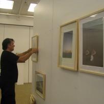 Etna Corbal accroche les photographies de ses installations végétales pour Les Rives de l'Art.