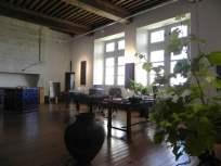 """Atelier d'Erik Samakh dans lequel (entre autres) jarre à eau de la Villa Médicis, pied de vigne relié à un capteur solaire, prototype de cube en panneaux solaires abritant un drône, amplificateur de chant de criquet (en verre sur la table), panneaux solaires... côtoient le matériel de l'artiste """"Studiolo"""", Erik SAMAKH, 2015 ; expo de fin de """"Résidence de l'Art en Dordogne""""-Biennale EpHémères #5 ; château de Monbazillac ; photo ©Les Rives de l'Art."""